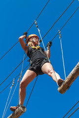 young girl in a mountain helmet walks at a height on wooden logs with ropes in an alpinist adventure park against a blue sky. training mountaineers in the mountains. rope park. leisure in nature