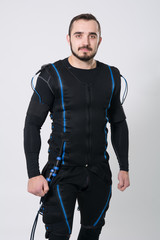 Young fitness man in an electric stimulation suit