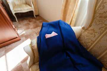 Expensive men's blue jacket lying on the couch with a pink handkerchief in his pocket. Closeup