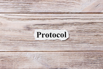 PROTOCOL of the word on paper. concept. Words of PROTOCOL on a wooden background