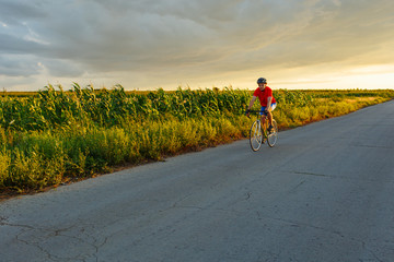 A cyclist rides on a road bicycle along field. In the background sunset sky.