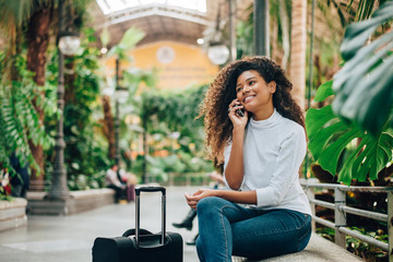 Young woman traveler with luggage talking on phone.