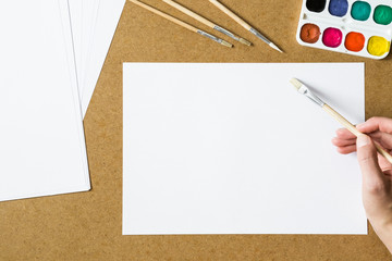 Artist painting a picture. White blank paper sheet with canvas and paint brushes. Empty place for a text or draw for good mood. Art concept.