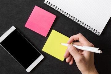 Woman writing in the colorful sticky notes. Working on the table. Empty place for a important ideas, plans, memories, messages, compliments or other text with positive mood. Reminder concept.