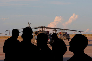 Soldiers from the 1st Armored Division, Combat Aviation Brigade, watch soldiers disassemble a CH-47 Chinook helicopter to ship to Puerto Rico in order to aid in recovery efforts following Hurricane Maria at Fort Bliss in El Paso