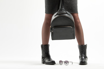 A girl in fashionable leather boots and a backpack in the studio