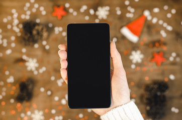 Female hands holding smart mobile phone with oled display on wooden background with Christmas snowflakes and snow. Happy New Year and Xmas Flat lay composition top view.