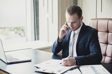 Businessman using Smartphone while working at office. Businessman have a busy time. Man working Concept. Vintage Tone.