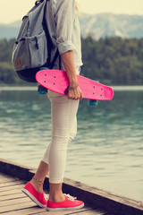 Attractive girl standing with her penny board outdoors.