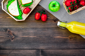 What bring for a picnic. Sanwiches, fruits, vegetables, juice on dark wooden background top view copyspace
