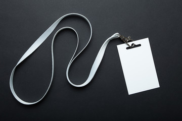 Blank badge mockup isolated on black. Plain empty name tag mock up hanging on neck with string. Name Tag, Corporate design.