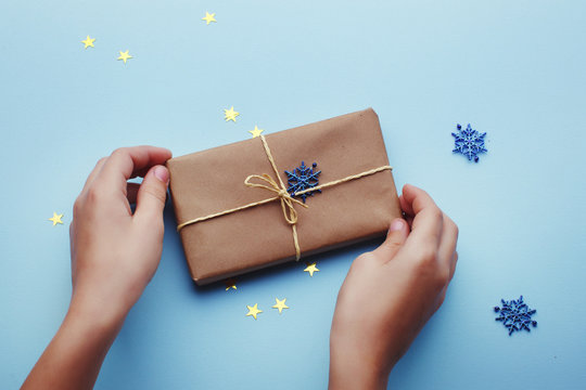 Gift box in the hands of a child on blue background with copy space