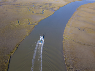 Aerial view of shrimp boat coming into port on coastal delta.