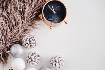 White Christmas background. Faux fur, rose gold clock, frosty pine cones, silver and white colored decoration balls. Minimalistic style. Copyspace for text, overhead, horizontal