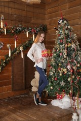 beautiful girl in a white shirt with a gift box is standing near a Christmas tree on a wooden wall background