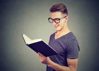 Portrait handsome man wearing glasses reading a book