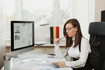 Beautiful business woman in suit and glasses working at computer with documents in light office, looking aside