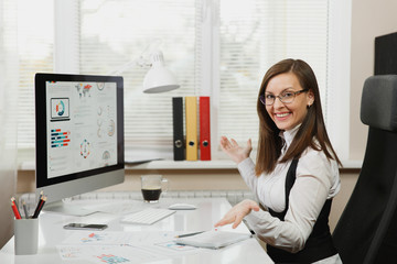 Beautiful smiling brown-hair business woman in suit and glasses working at computer with documents in light office, looking at the camera
