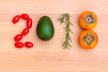 Year 2018 made of vegetables, herbs and fruits on wooden background.