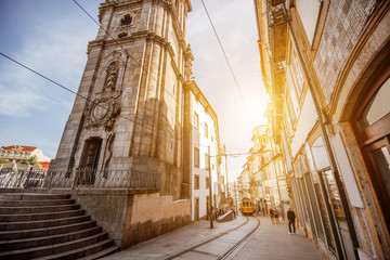 Street view with Clerics church tower with retro tram during the sunrise in Porto city, Portugal