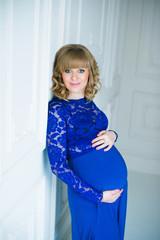 Happy pregnant woman in blue dress posing in studio