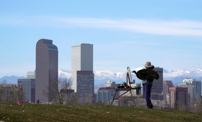 Dawn Cohen works on an oil painting of downtown Denver, in City Park in Denver