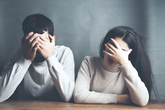 sad young couple sitting in table