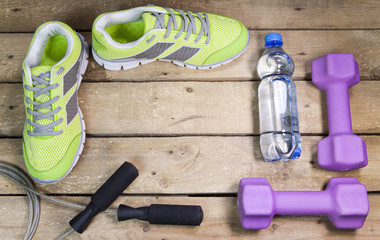 Sports sneakers, dumbbells, drinking water on a wooden background,  flat lay