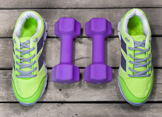 Sports sneakers, dumbbells, on a wooden background,  flat lay