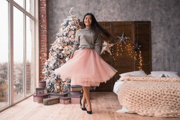 christmas , winter holidays and people concept - young asian girl dances near Christmas tree