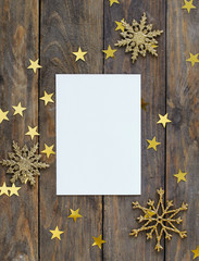 Mock up greeteng card on wood rustic background with Christmas decorations glitter snowflakes and gold stars confetti. Invitation, paper. Place for text flat lay