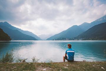 tourist cyclist rests near the mountain lake Lago di Ledro in Italy in the vicinity of lago di Garda