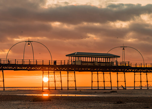 Birds fly over Southport Pier as the sun sets