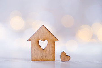 Wooden house with hole in the form of heart with little heart on light bokeh background