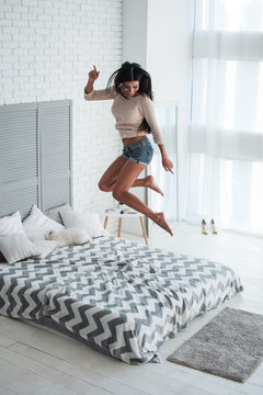 Pure joy. Top view full length of beautiful young woman jumping on bed with smile indoors