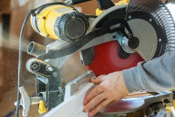 handsome man carpenter using a circular saw while installing wood