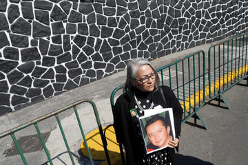The mother of of missing person Fernandez displays his picture during a protest outside Los Pinos presidential residence in Mexico City