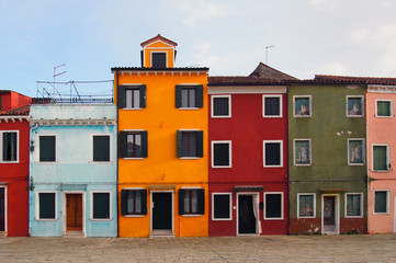 street of colourful houses in burano venice in summer with blue sky