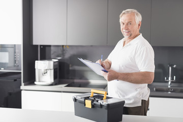 The man is in the kitchen. He holds a form for papers in his hands. Next to him stands a black box for the instrument.