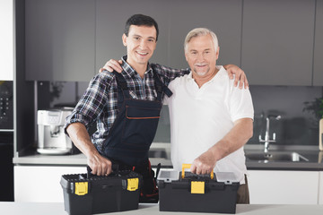 Two men of plumbers stand in the kitchen and pose with black toolboxes.