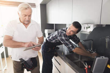 Two plumbers are standing in the kitchen. An elderly man looks something on his tablet while young man repairs the tap.