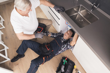 Two plumbers are prepared to repair the water filter. One of them is under the sink, the second is nearby.
