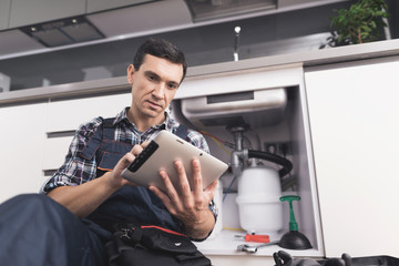 The plumber sits next to the kitchen sink on the floor and looks at the tablet for repair instructions.