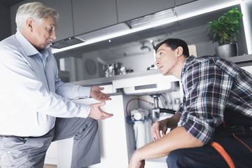 A man plumber speaks with a client who is dissatisfied with the work done.
