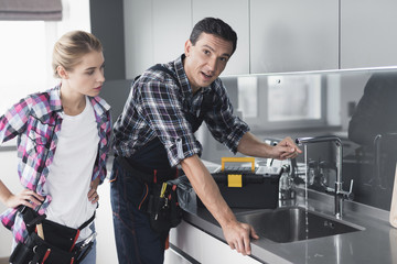 A man and a woman plumber repair a kitchen faucet from the client at home.