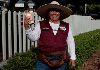 A money changer holds a stack of Nicaraguan currency while posing for a photo in Managua
