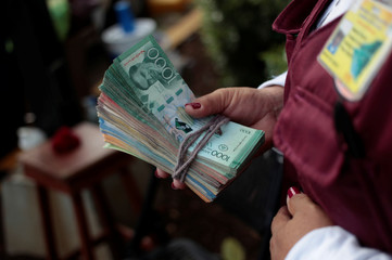 A money changer holds a stack of Nicaraguan currency on a street in Managua