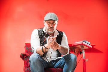Bearded male tattoo master posing with tattoo machine gun