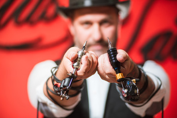 Bearded male tattoo master with tattoo machine gun in hands