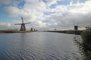 Historical windmills at the Kinderdijk area along a canal in the Netherlands with Blue sky and big white clouds